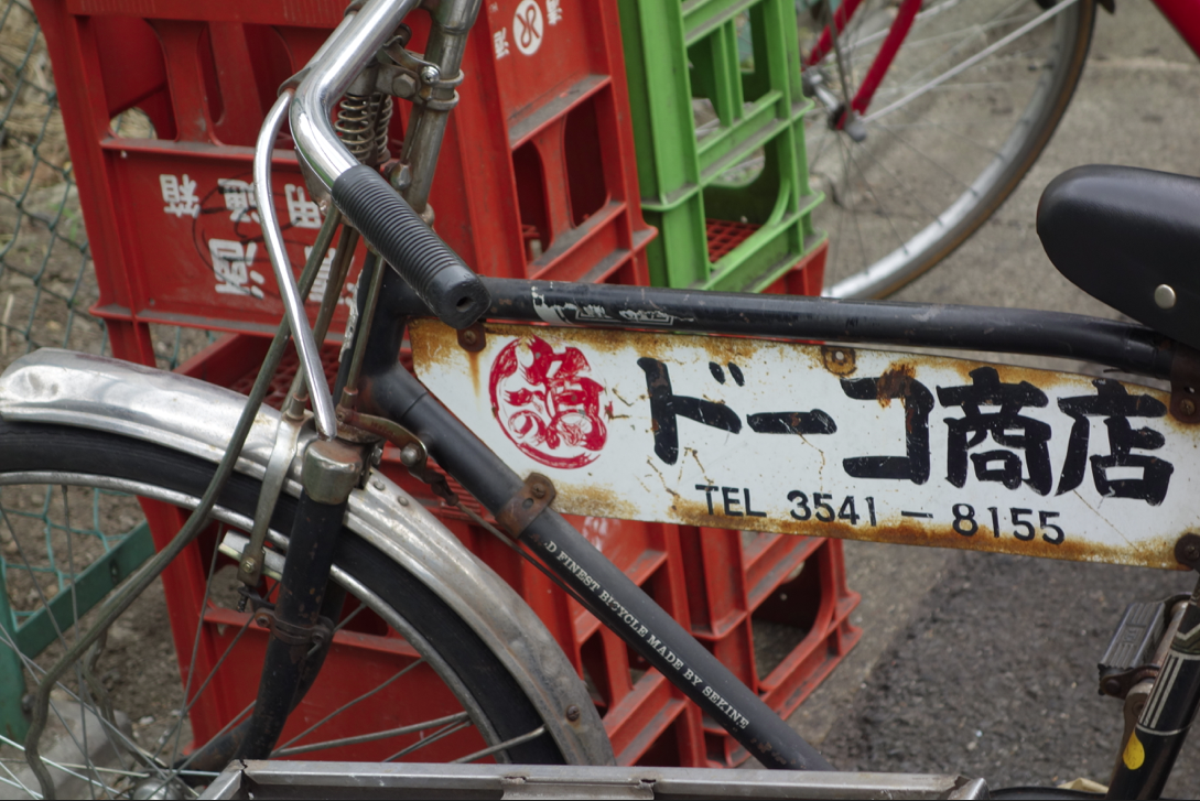 pic of delivery bicycle with rusty sign in Chinese