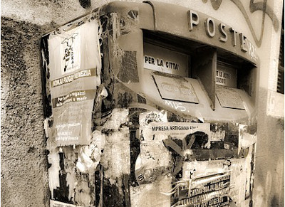 image of postbox covered by wheat-pasted flyers
