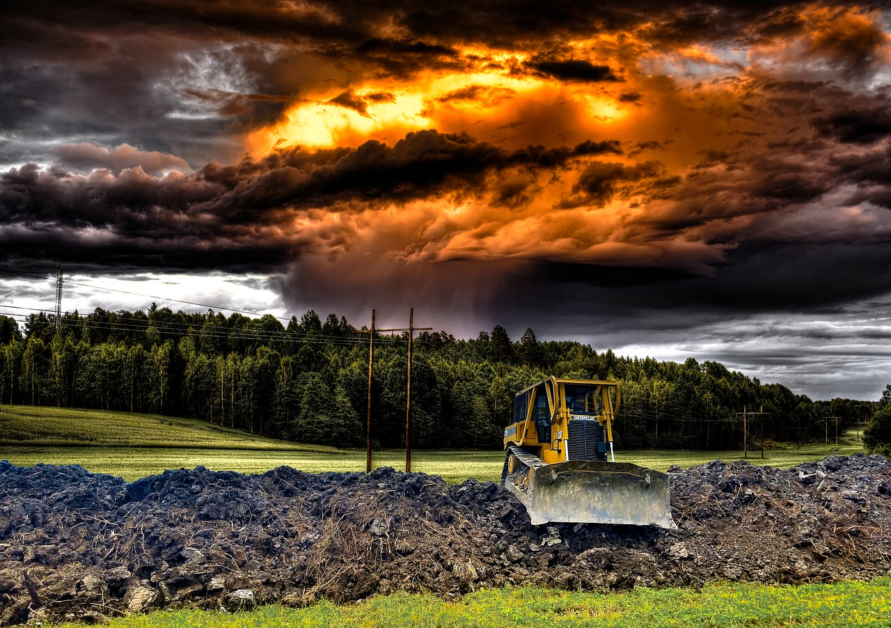 pic of a bulldozer in rustic setting beneath eerie sky